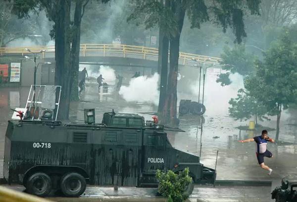 Manifestante tira piedras a la policía en la Universidad Nacional.